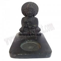 Posa velas con Buda sentado.